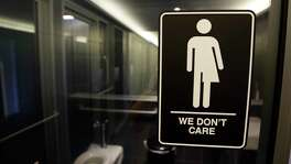 "FILE - This Thursday, May 12, 2016, file photo, shows a sign outside a restroom at 21c Museum Hotel in Durham, N.C. The Associated Press has determined that North Carolina's law limiting LGBT protections will cost the state more than $3 billion in lost business over a dozen years.That's despite Republican assurances that the ""bathroom bill"" isn't hurting the economy. (AP Photo/Gerry Broome, File)"