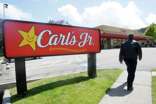 FILE - In this May 25, 2011, file photo, a man walks past a sign for a Carl's Jr. restaurant in San Bruno, Calif. The fast food chain released an advertisement on March 29, 2017, suggesting it intends to ditch its racy advertising in an effort to focus on its food. (AP Photo/Jeff Chiu, File)