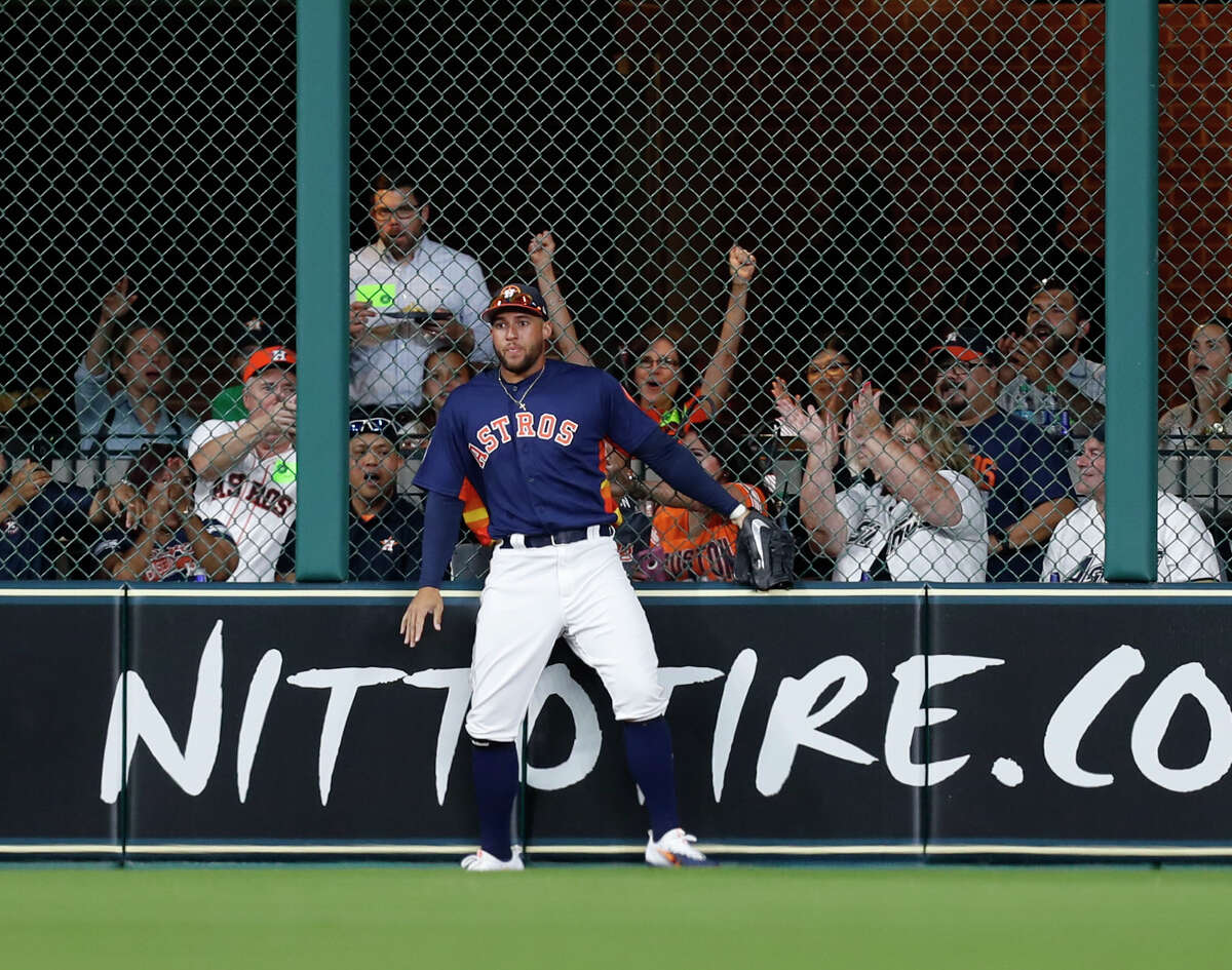 Fans react as Houston Astros right fielder George Springer (4) catches Chicago Cubs third baseman Kris Bryant's fly out at the center field fence during the second inning of an MLB exhibition game at Minute Maid Park, Thursday, March 30, 2017, in Houston. ( Karen Warren / Houston Chronicle )
