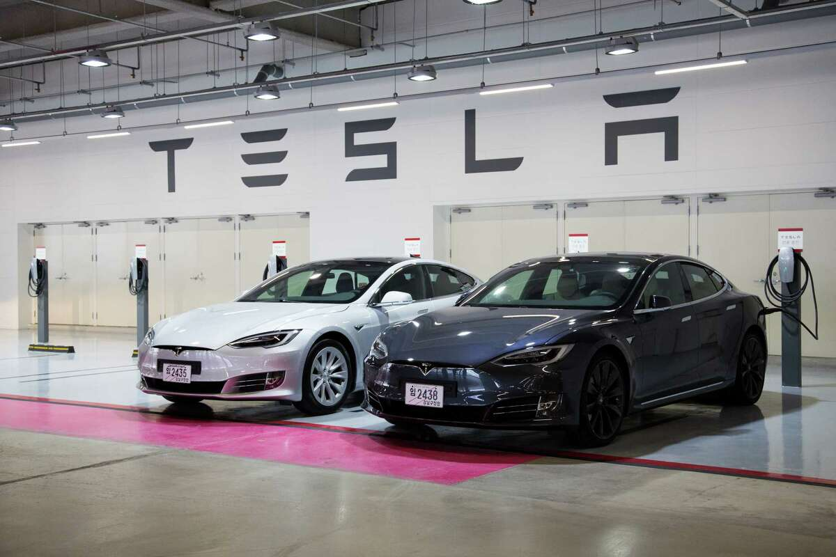 Tesla vehicles are at a charging station. Texas drivers aren't barred from buying Teslas, but they're subject to some limits when ordering.