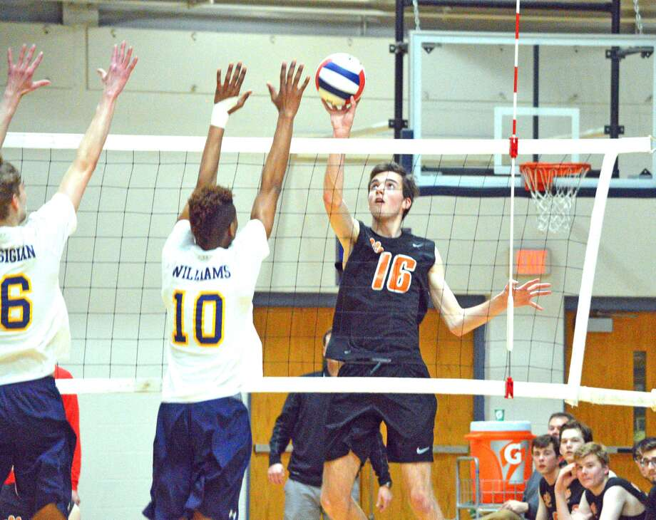 Edwardsville senior Jack Grimm, right, attempts a kill during the first game of Thursday's Southwestern Conference match at O'Fallon.
