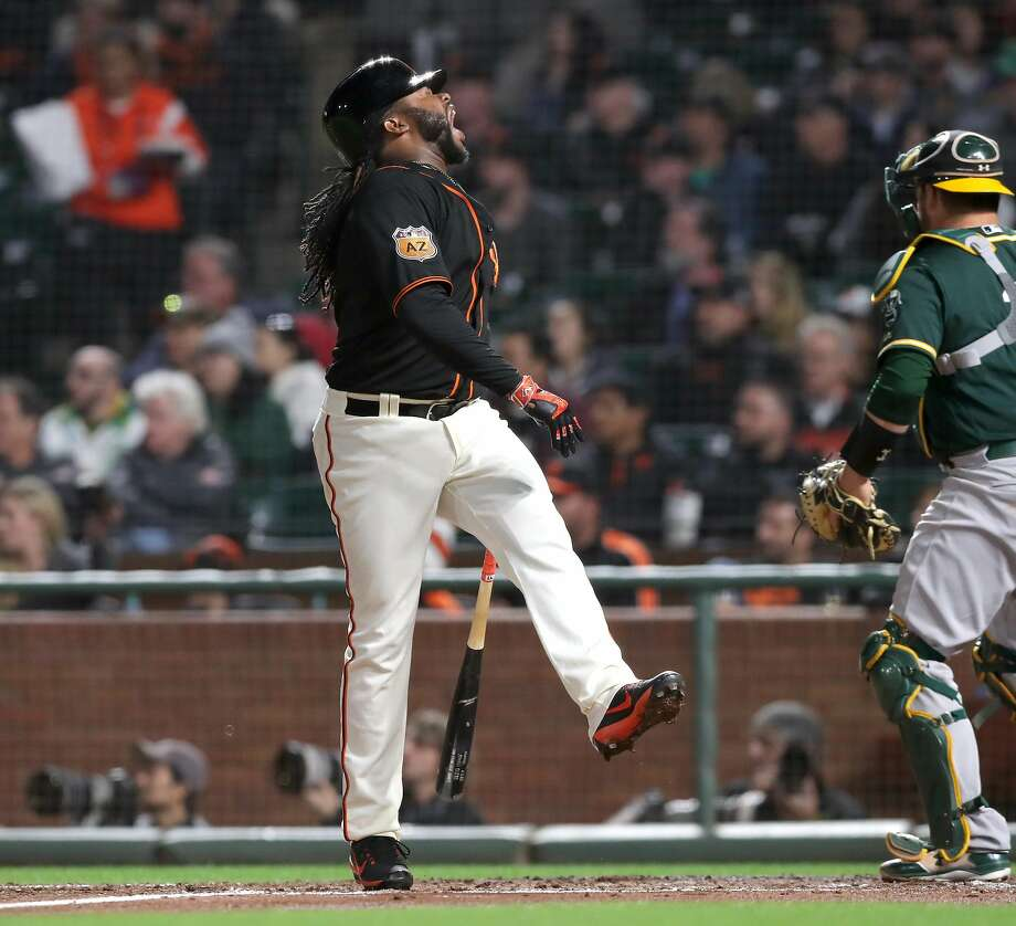 Giants' Johnny Cueto jumps away from the plate after fouling off a ball that hit him in the fourth inning, as the San Francisco Giants take on the Oakland Athletics in pre-season action at AT&T Park  in San Francisco, Ca.as seen on Thurs. Mar. 30, 2017. Photo: Michael Macor / The Chronicle