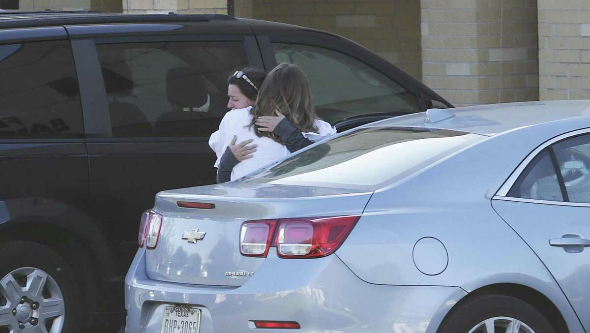 Church members embrace in the parking lot of the New Braunfels First Baptist Church on March 30, 2017. A trickle of visitors were at the church in the day.