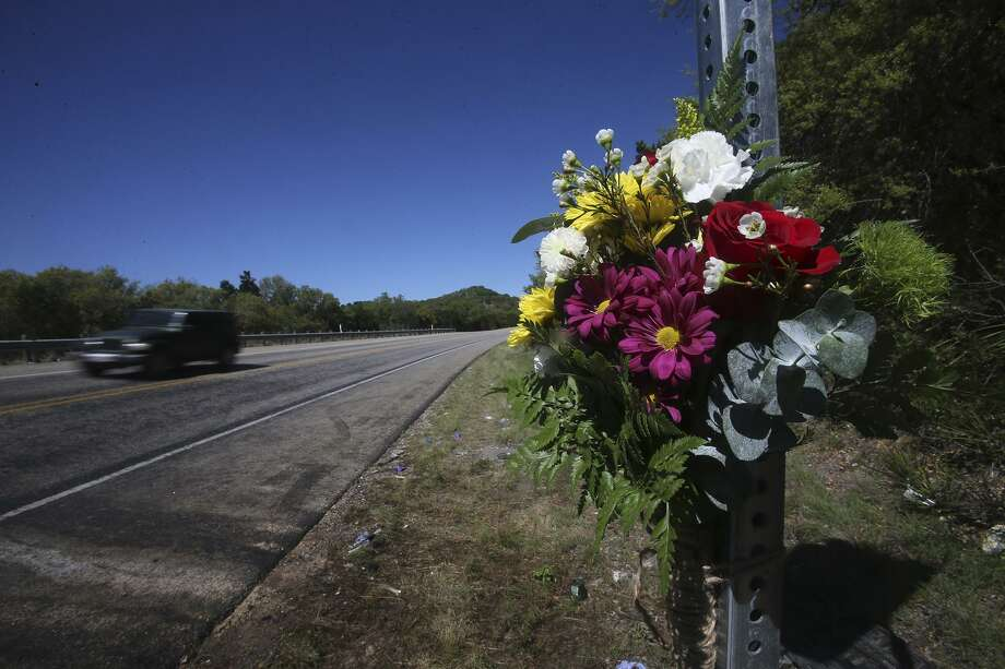 Flowers have been placed on a road sign where 13 people died in a wreck involving a small church bus and a pickup. Photo: John Davenport /