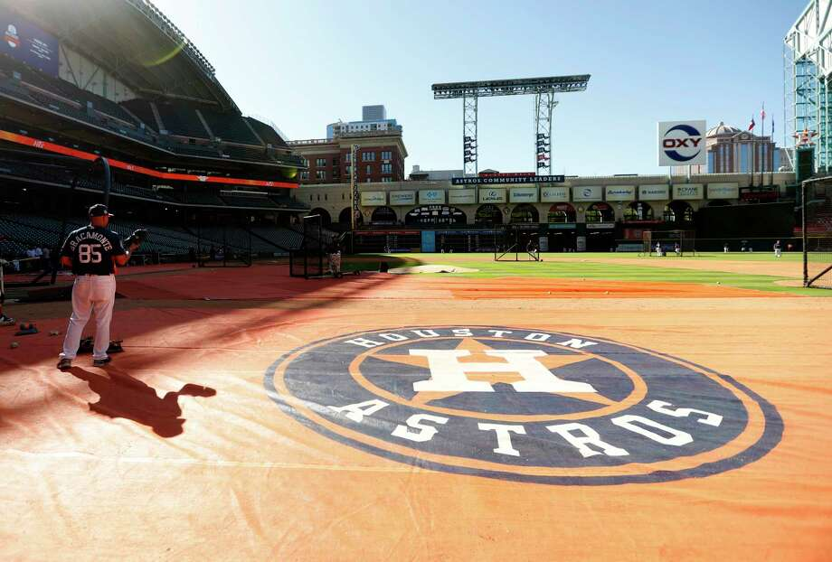 Houston Astros bullpen catcher Javier Bracamonte casts a shadow on the ground covering on the field during batting practice before the start of an MLB exhibition game at Minute Maid Park, Thursday, March 30, 2017, in Houston.  ( Karen Warren / Houston Chronicle ) Photo: Karen Warren, Staff Photographer / 2017 Houston Chronicle