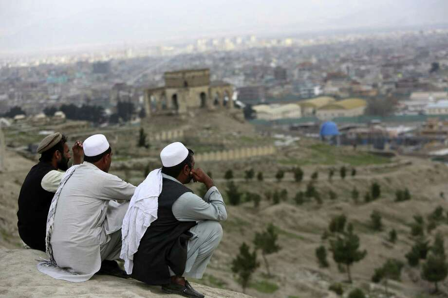 "In this March 27, 2017, file photo, men sit on the Nadir Khan hilltop overlooking Kabul, Afghanistan. As America's 16-year war in Afghanistan drags on, Russia is resurrecting its own interest in the ""graveyard of empires."" The jockeying includes engaging the Taliban and leading a new diplomatic effort to tackle Afghanistan's future, all while Washington leaves the world guessing on its strategy for ending the conflict. (AP Photo/Rahmat Gul) Photo: Rahmat Gul, STF / Associated Press / Copyright 2017 The Associated Press. All rights reserved."