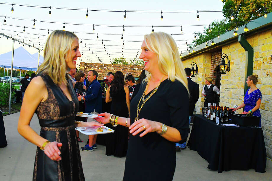 Natalie Johnson and Leslie Maloney stop to the dine on the food serve at the wine tasking event. Photo: Tony Gaines, Photographer
