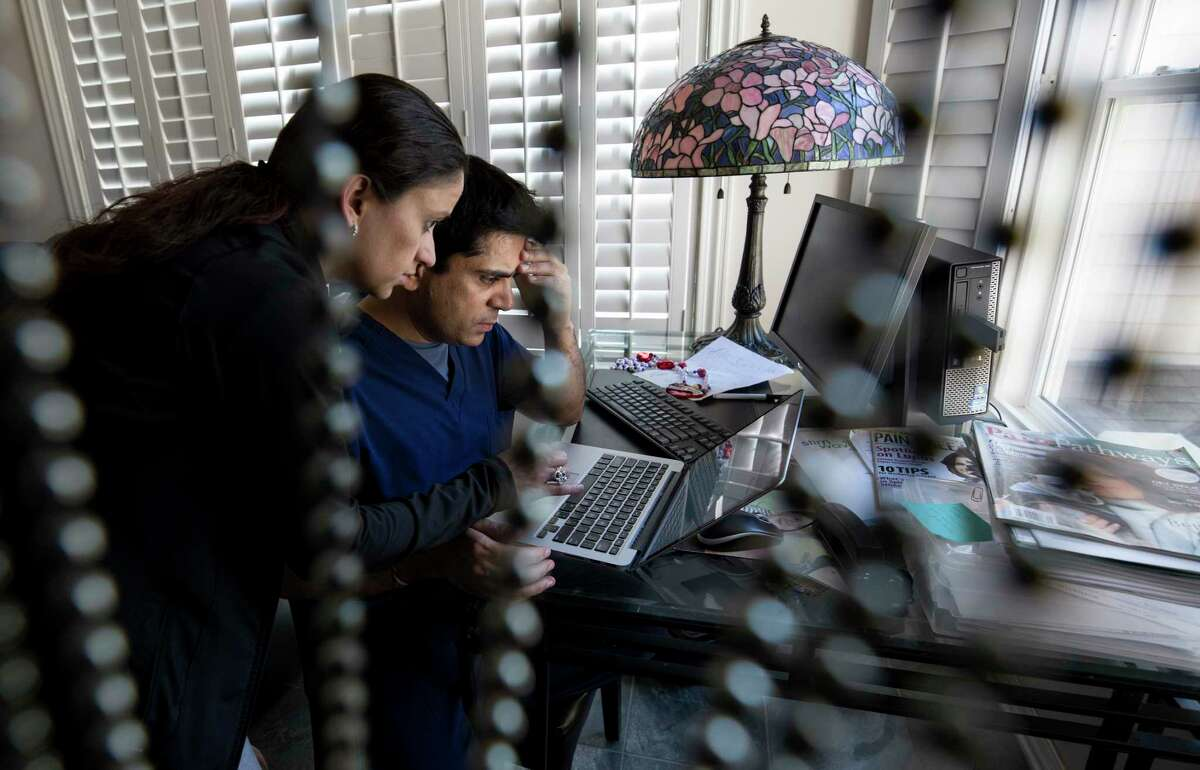 Doctors Monika Ummat, left, her husband Pankaj Satija, right, take care of loose ends before leaving to the U.S. Customs and Border Protection Deferred Inspection building Thursday, March 30, 2017, in Houston. Satija and Ummat were facing possible immediate return to India, but were granted 90 days to resolve their immigration paper-work.