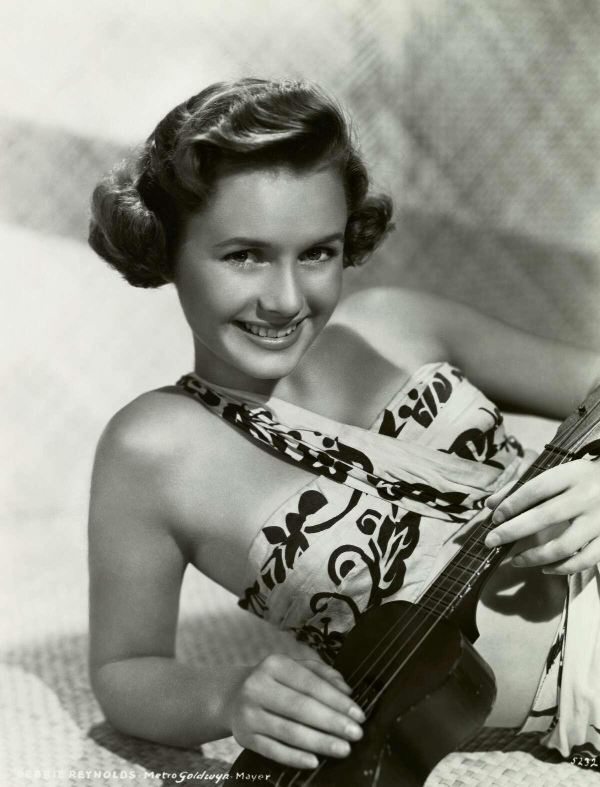 Debbie Reynolds holding a Ukelele.