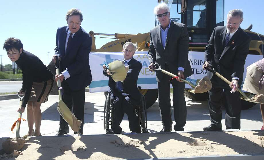 Texas Governor Greg Abbott (center, seated) and Texas Transportation Commissioner J. Bruce Bugg, Jr. (left of Abbott) break ground on an expansion of U.S. Highway 281 that will help to reduce traffic congestion in the northern part of San Antonio. The first of two phases stretching eight miles will get underway in May. It will add non-tolled expressway lanes as well as high occupancy vehicle lanes from Loop 1604 to Stone Oak Parkway. On the far left is State Senator Donna Campbell. To the right of Abbott is Representative Lyle Larson and on the far right is Texas Department of Transportation executive director James Bass. Photo: John Davenport, STAFF / San Antonio Express-News / ©San Antonio Express-News/John Davenport