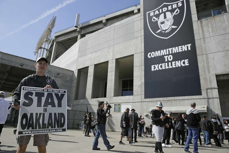 John P. Kelleher holds up a sign outside the Oakland Coliseum before the start of a rally to keep the Raiders from moving, on March 25, 2017. Photo: Eric Risberg, Associated Press
