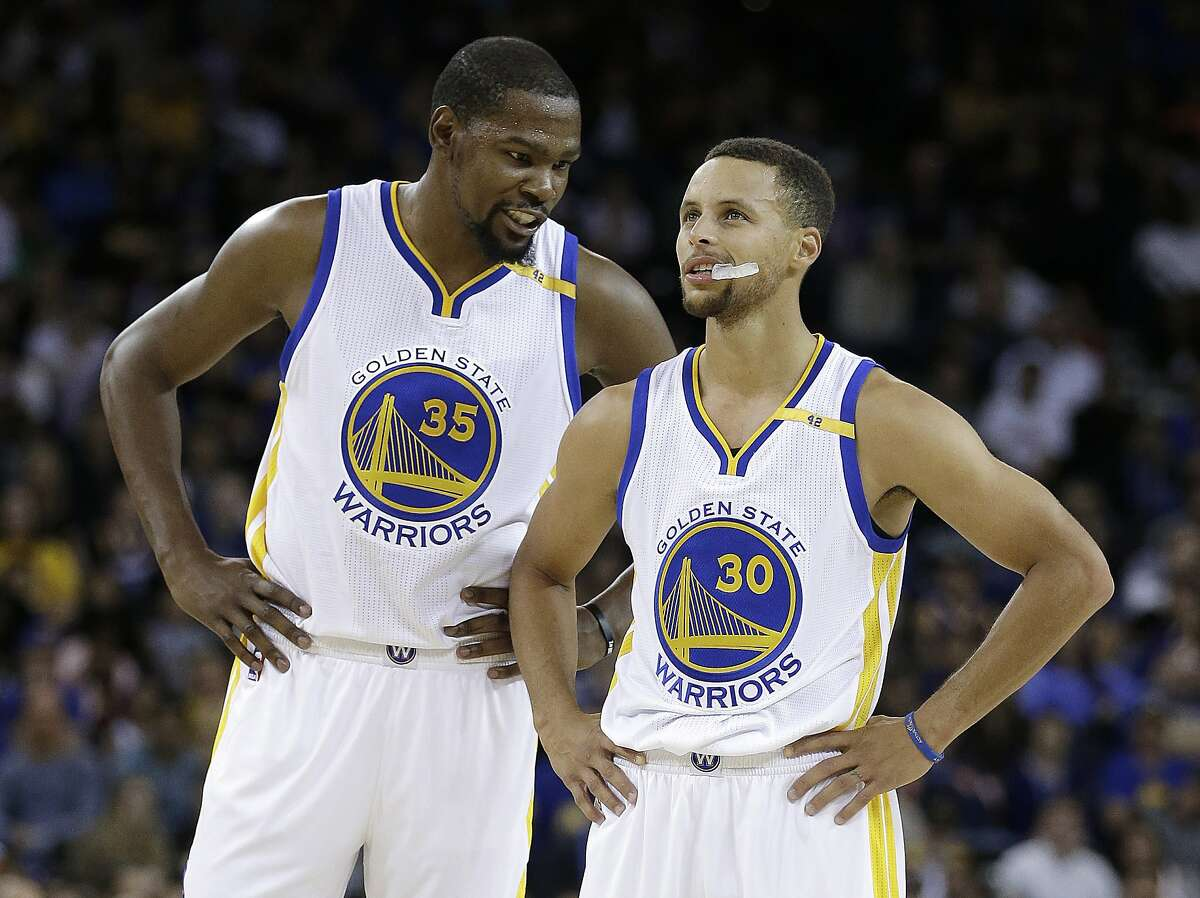 FILE - In this Oct. 4, 2016, file photo, Golden State Warriors' Kevin Durant, left, speaks with Stephen Curry (30) during the first half of a pre-season NBA basketball game against the Los Angeles Clippers in Oakland, Calif. For everyone who questioned whether Stephen Curry and Kevin Durant could coexist and put their egos aside for the greater good, the Golden State Warriors are a couple of months into the season and the superstars are thriving together. (AP Photo/Ben Margot)