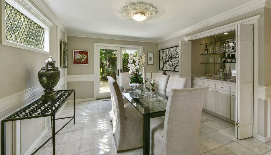 The formal dining room has a wet bar and dual doors opening to the garden. / ONLINE_CHECK