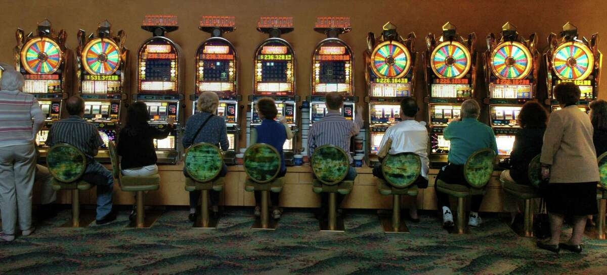 Gamblers huddle around a row of slot machines at Mohegan Sun Casino
