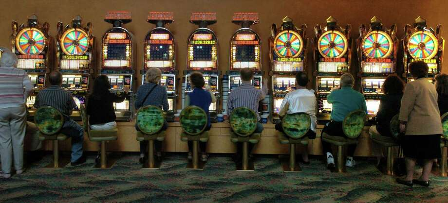 Gamblers huddle around a row of slot machines at Mohegan Sun Casino Photo: Hearst Connecticut Media File Photo