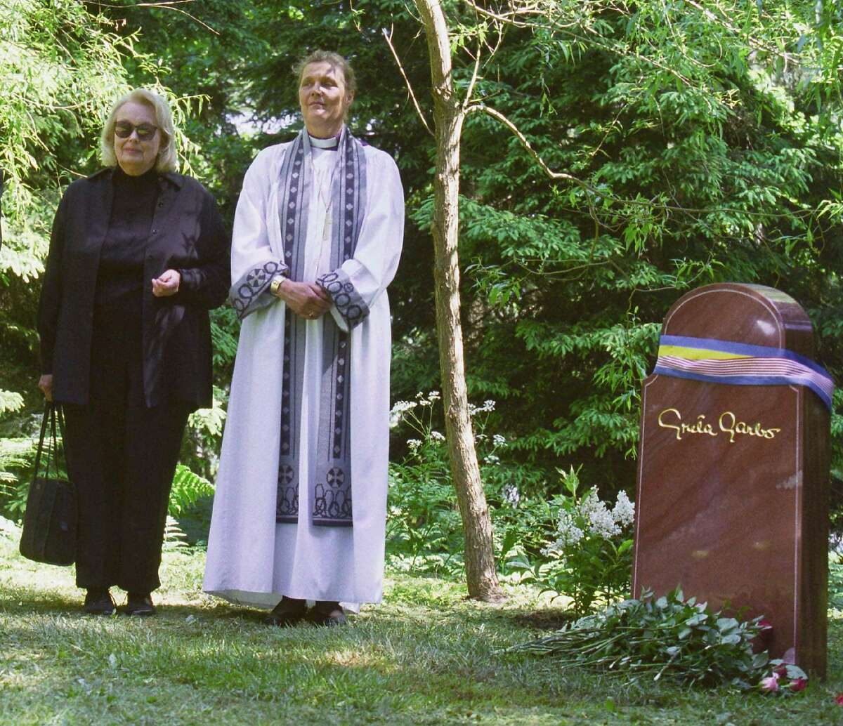 Gray Reisfield, left, and Bishop Caroline Krook stand next to the tombstone of Greta Garbo after the memorial service at the Woodland Cemetery in Stockholm, Sweden, Thursday June 17, 1999. Greta Garbo's ashes were interred in the Woodlands Cemetery Wednesday. Gray Reisfield is the niece and only heir of the 1930s Hollywood film legend. (AP photo/Pressens Bild/Tobias Rostlund) SWEDEN OUT MAGAZINES OUT NO SALES TV OUT