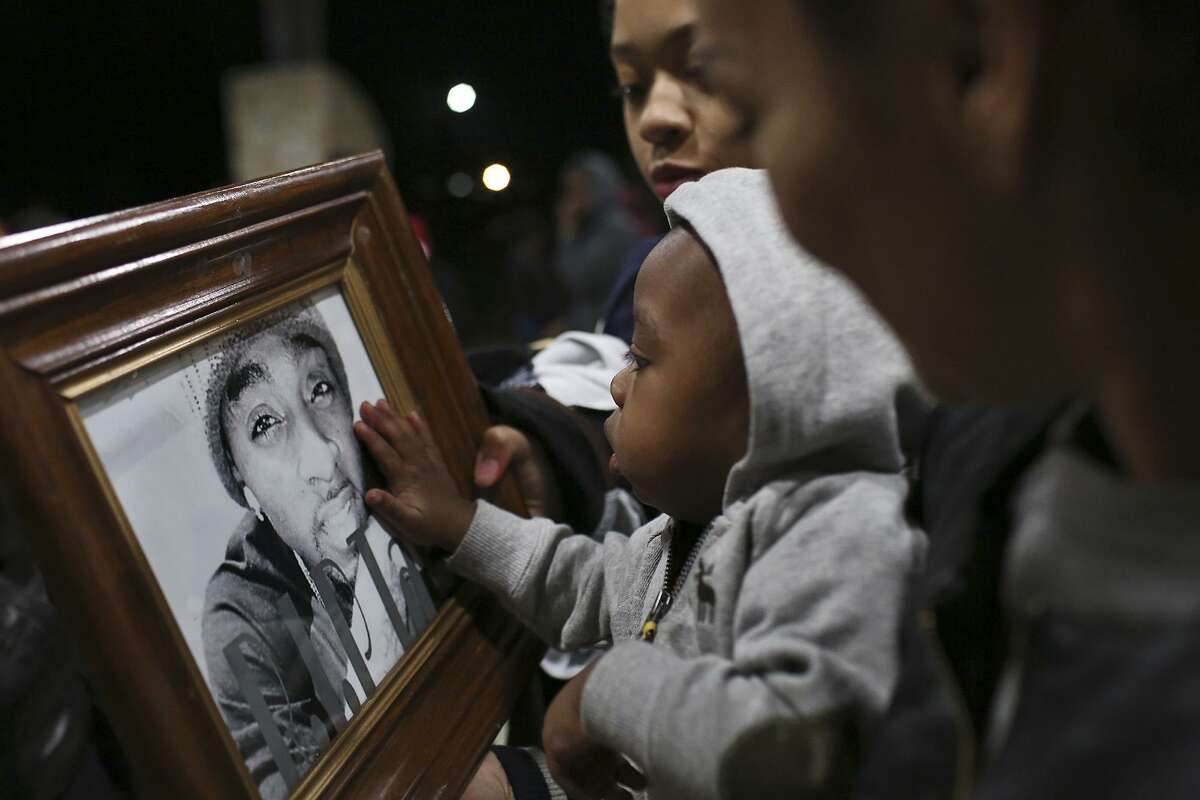 In 2015, Jaymar Price touches a photograph of his father, Vontay Price, one of two men killed on Martin Luther King Jr. Day. The violence on the East Side is one of the costs of the city's economic segregation.