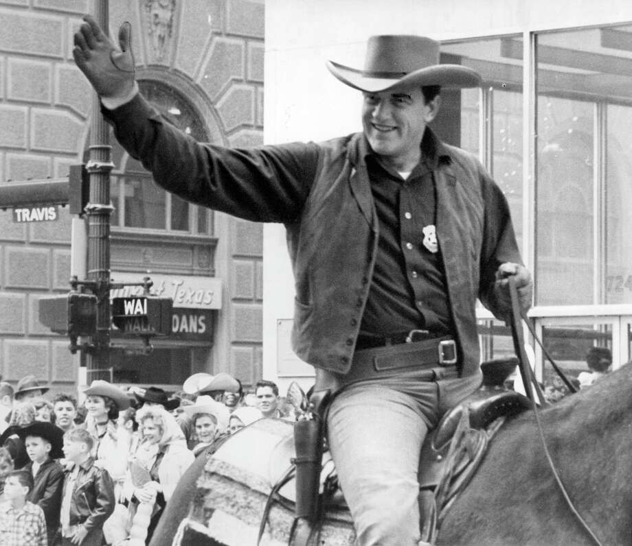 "Actor James Arness, outfitted as Marshall Matt Dillon from the popular television program ""Gunsmoke,"" waves to the crowd in the Houston stock show parade in 1959. A reader has discerned a curious element of the show from watching   reruns. Photo: Houston Chronicle File Photo / Houston Post files"