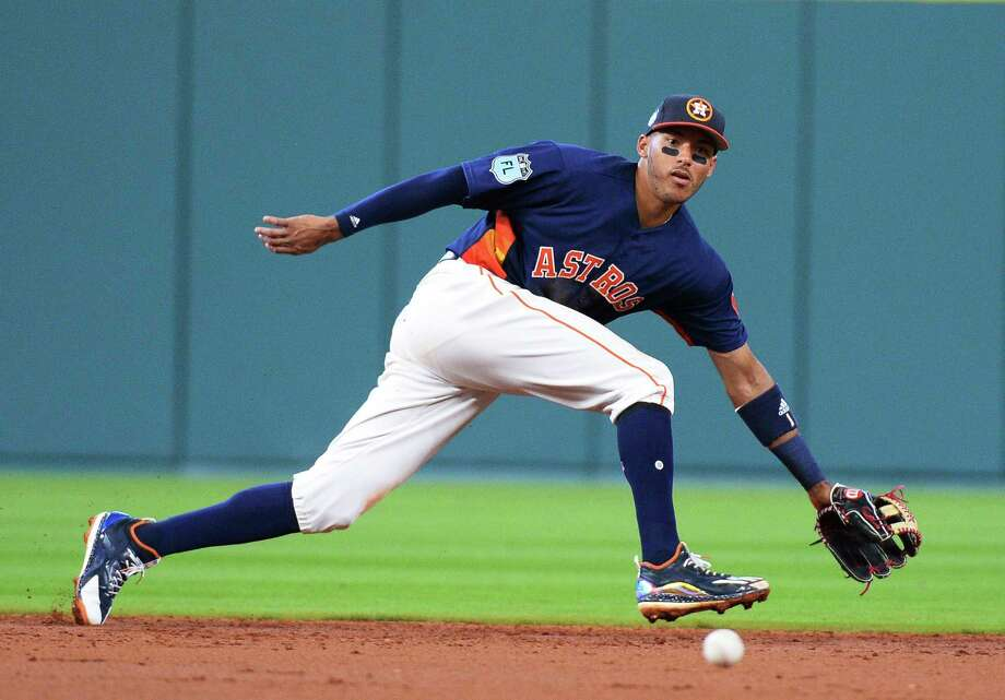 Houston Astros shortstop Carlos Correa can't get to a ball hit by Chicago Cubs' Kyle Schwarber for a single during the third inning of an exhibition baseball game Friday, March 31, 2017, in Houston. (AP Photo/George Bridges) Photo: George Bridges, FRE / FR171217 AP