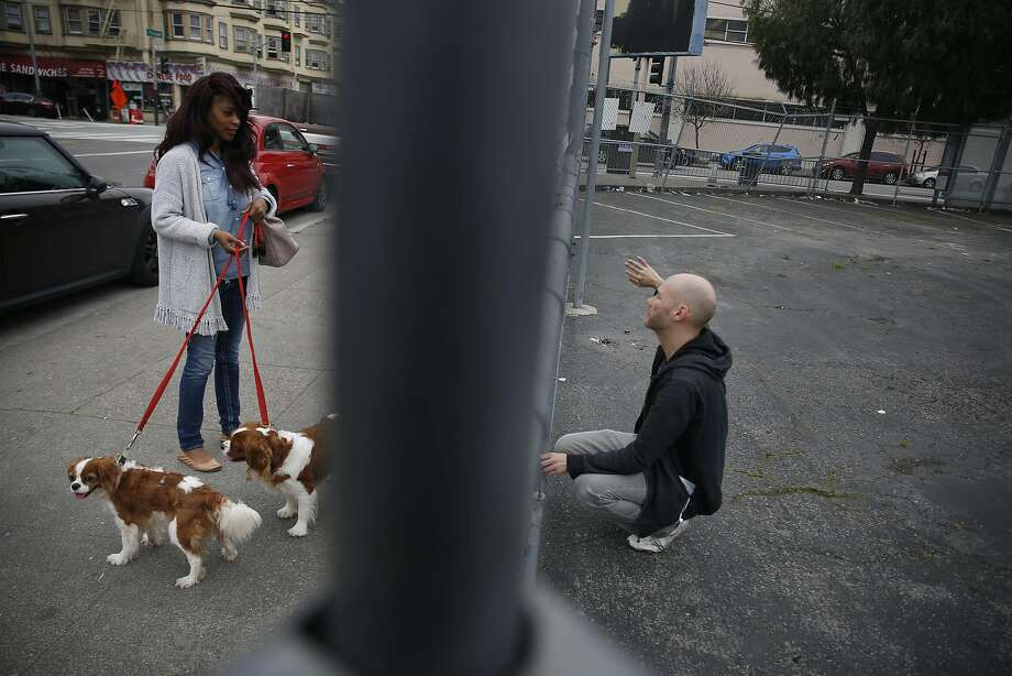 "Tara Brooks (left), who says she has been homeless for eight months, visits with artist Brian Singer as he fixes his installation, ""Home Street Home,"" on Folsolm Street in the Mission District. Photo: Lea Suzuki, The Chronicle"