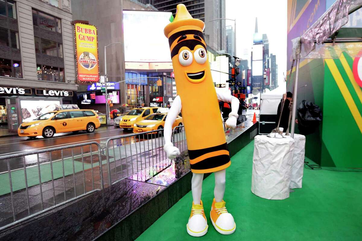 """A dandelion crayon character poses for photos during a Crayola event in New York's Times Square, Friday, March 31, 2017. Crayola announced Friday, National Crayon Day, that it's replacing the color dandelion in its 24-pack with a crayon in """"the blue family."""" (AP Photo/Richard Drew)"""