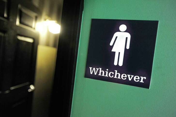 """A gender neutral sign posted at a public bathroom last year in Durham, N.C., reflects the firestorm of criticism the """"bathroom bill"""" brought to the state."""