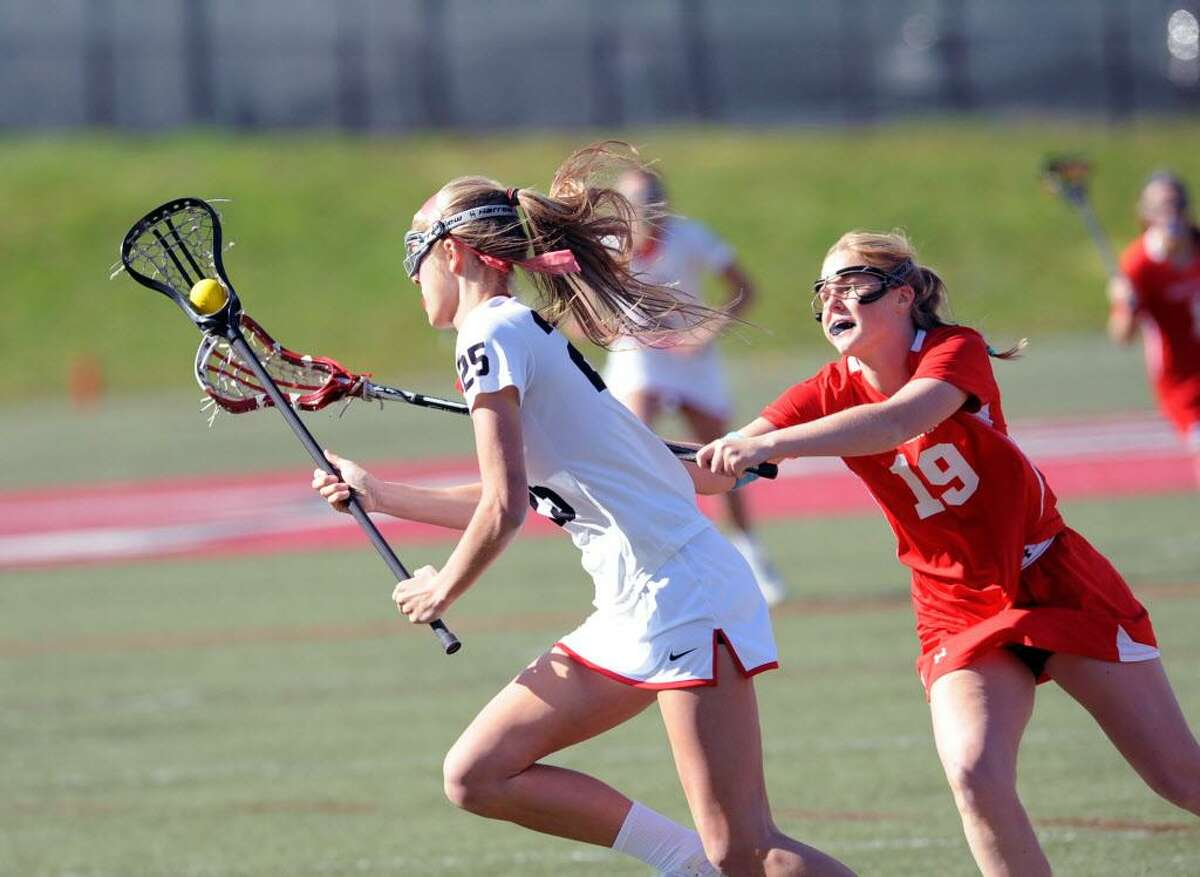 New Canaan's Campbell Armstrong, left, advances the ball as Greenwich's Emily Hopper pursues during a game April 12 at New Canaan.