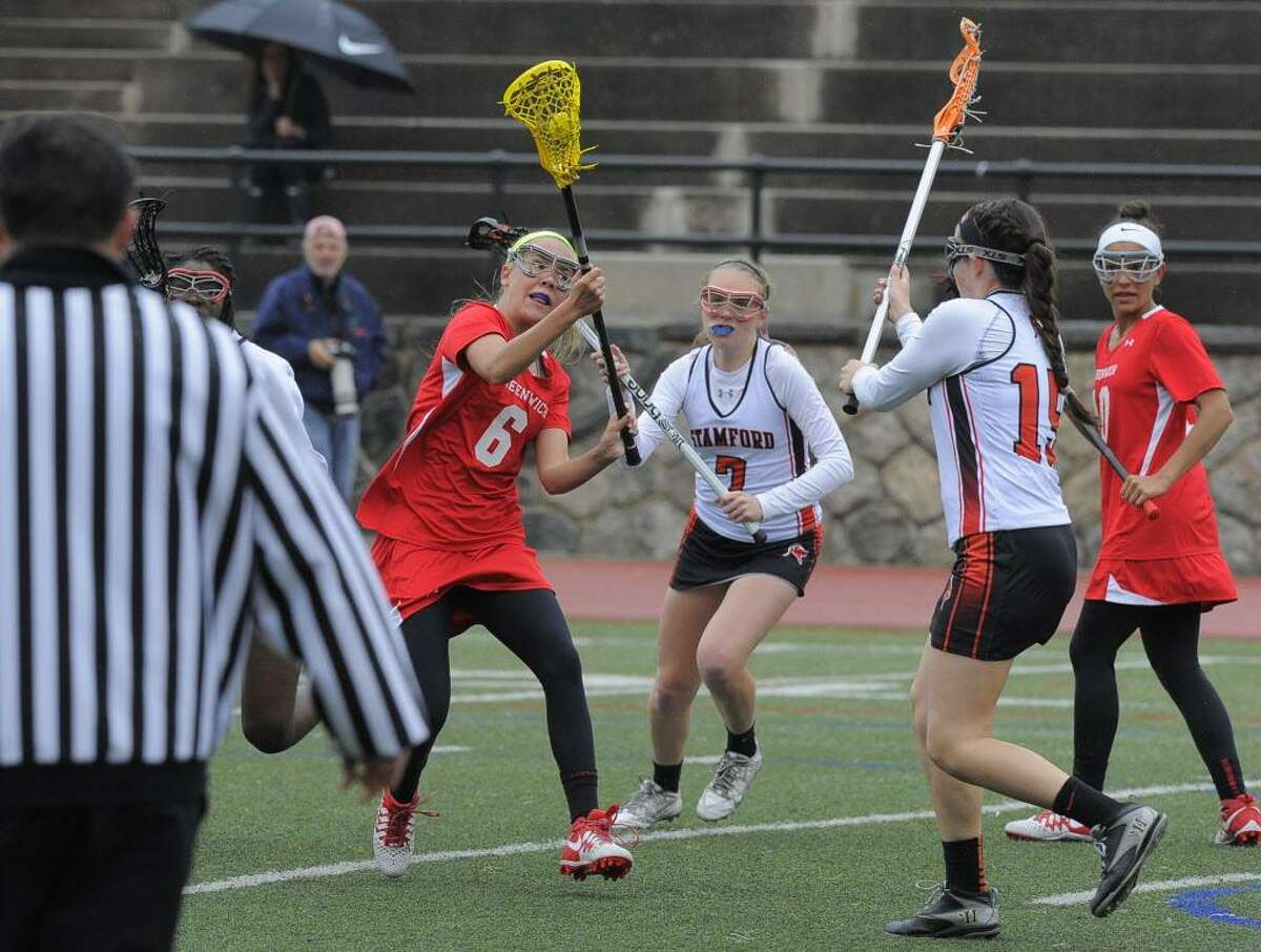 Greenwich's Erika Bloes fires a shot on goal past Stamford's Mackenzie Brown during a game April 26. Greenwich defeated Stamford 15-7.