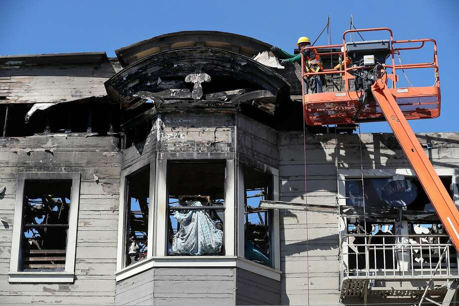 Workers begin to stabilize the Oakland Halfway house that burned, killing four. Photo: Michael Macor, The Chronicle