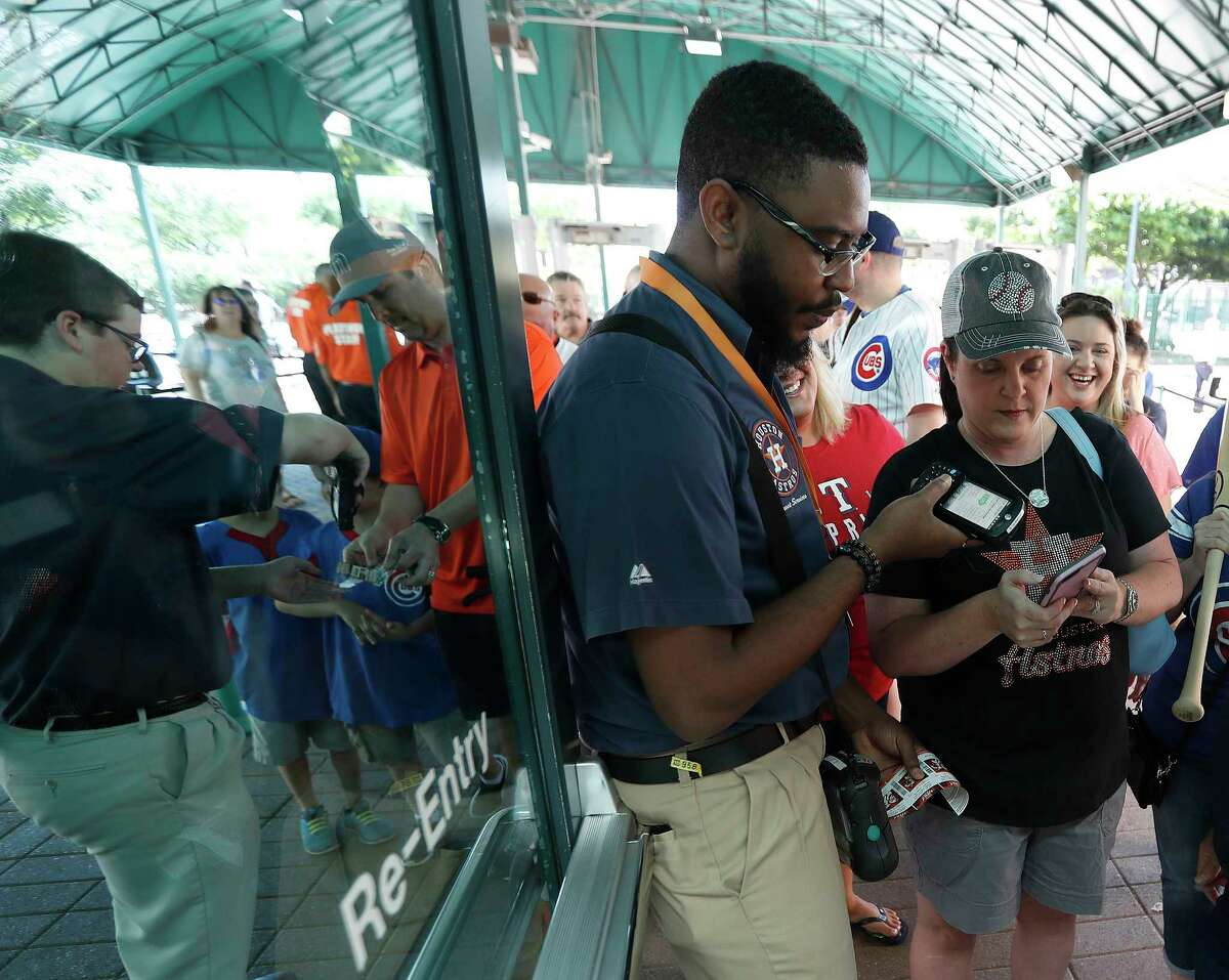 Astros employee Johnson Kalu scans Sharon Lemon's phone for entry to Minute Maid Park for a recent Astros exhibition game.