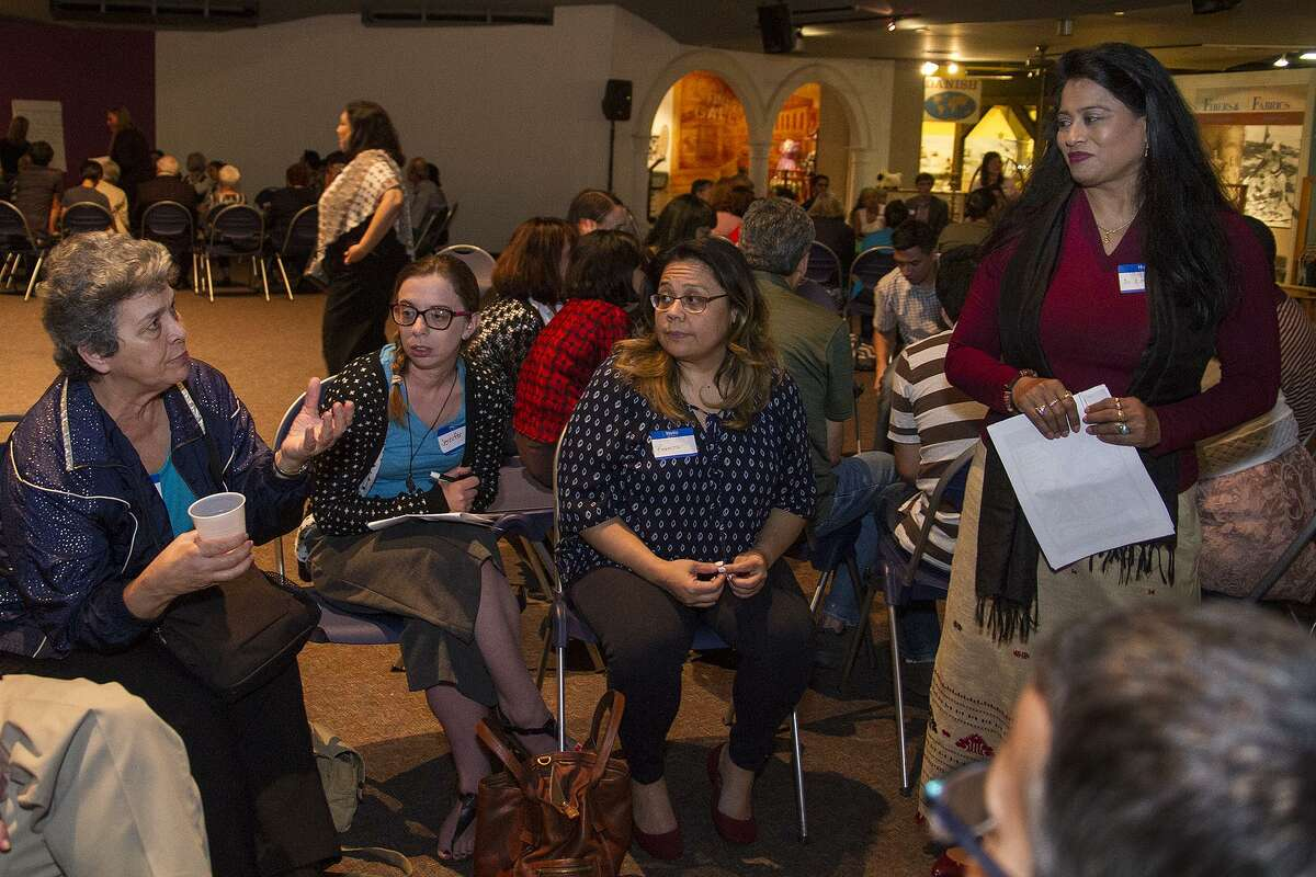 Toni Gustafson (seated left), talking with Dr. Lopita Nath (standing) as part of an event called Cultural Conversations: Refugee in San Antonio, an open discussion about issues related to the local refugee community, Monday, March 27, 2017 at the UTSA Institute of Texan Cultures.