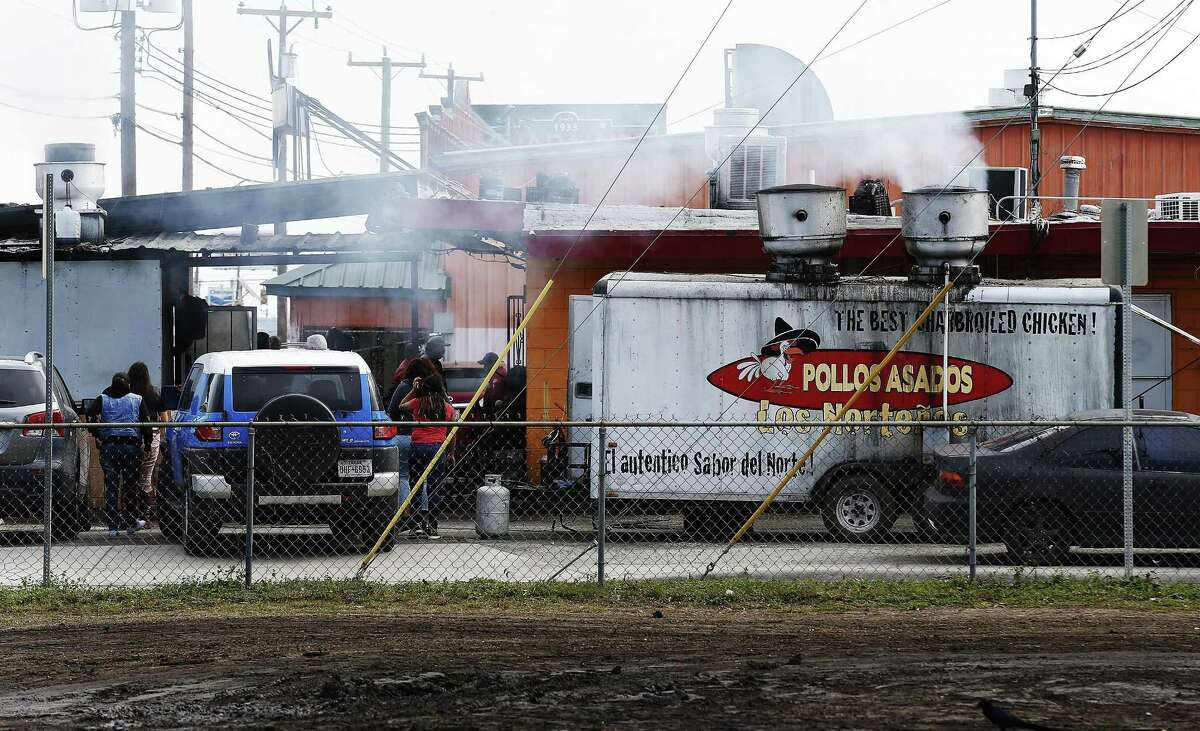 Smoke emanates from a portable cook stand as well as from an affixed building at Pollos Asados Los Nortenos restaurant on Rigsby Avenue on Thursday, Jan. 14, 2016. Last week, the company agreed to install more pollution controls at the restaurant. (Kin Man Hui/San Antonio Express-News)