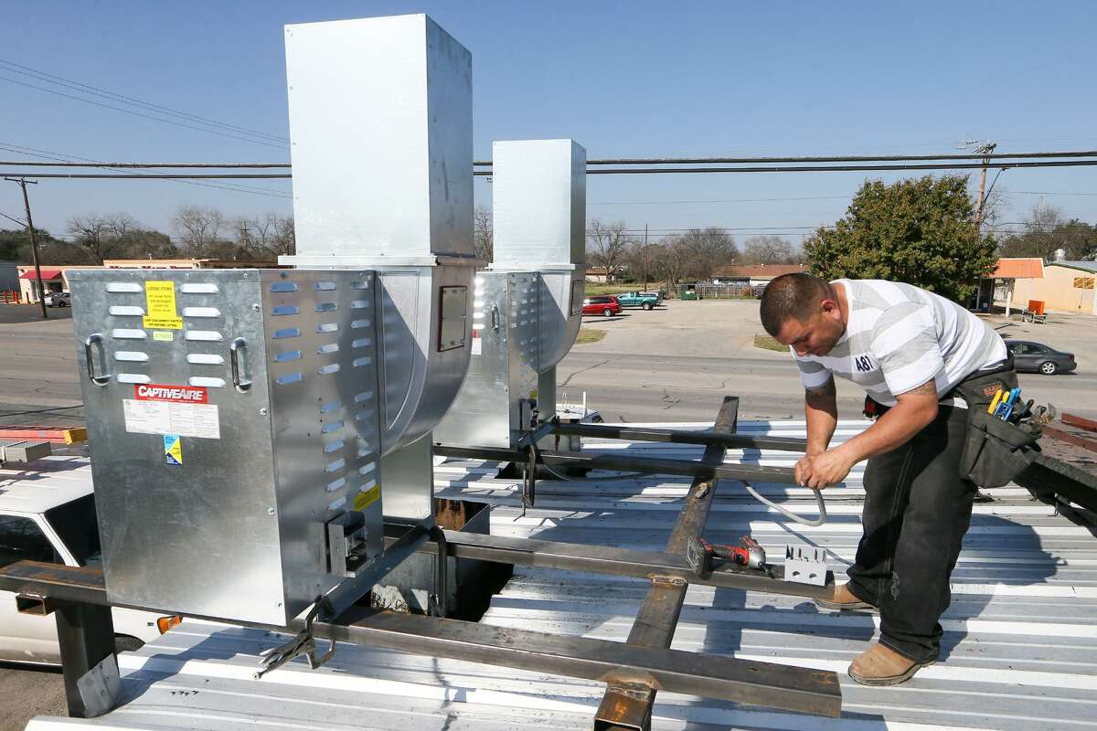 Omar Torres, with San Antonio Alliance Electric, runs wiring for two high velocity exhaust fans on the roof of the smokehouse at Pollos Asados Los Nortenos, 4642 Rigsby Ave., on Monday, Feb. 1, 2016. Owner Frank Garcia has installed new fire suppression and exhaust systems and hopes to reopen the popular Southeast Wide restaurant on Wednesday. MARVIN PFEIFFER/ mpfeiffer@express-news.net