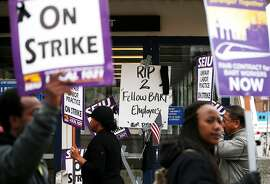 OAKLAND, CA - OCTOBER 21:  Striking Bay Area Rapid Transit (BART) workers picket in front of a sign honoring two BART workers who were struck and killed by a BART train over the weekend while servicing tracks near the Walnut Creek station on October 21, 2013 in Oakland, California.  BART workers continue to strike after contract negotiations between BART management and the transit agency's two largest unions fell apart last week. Management and unions agreed on the financial specifics of the contract but differed on workplace safety rules. An estimated 400,000 commuters ride BART each day.  (Photo by Justin Sullivan/Getty Images)
