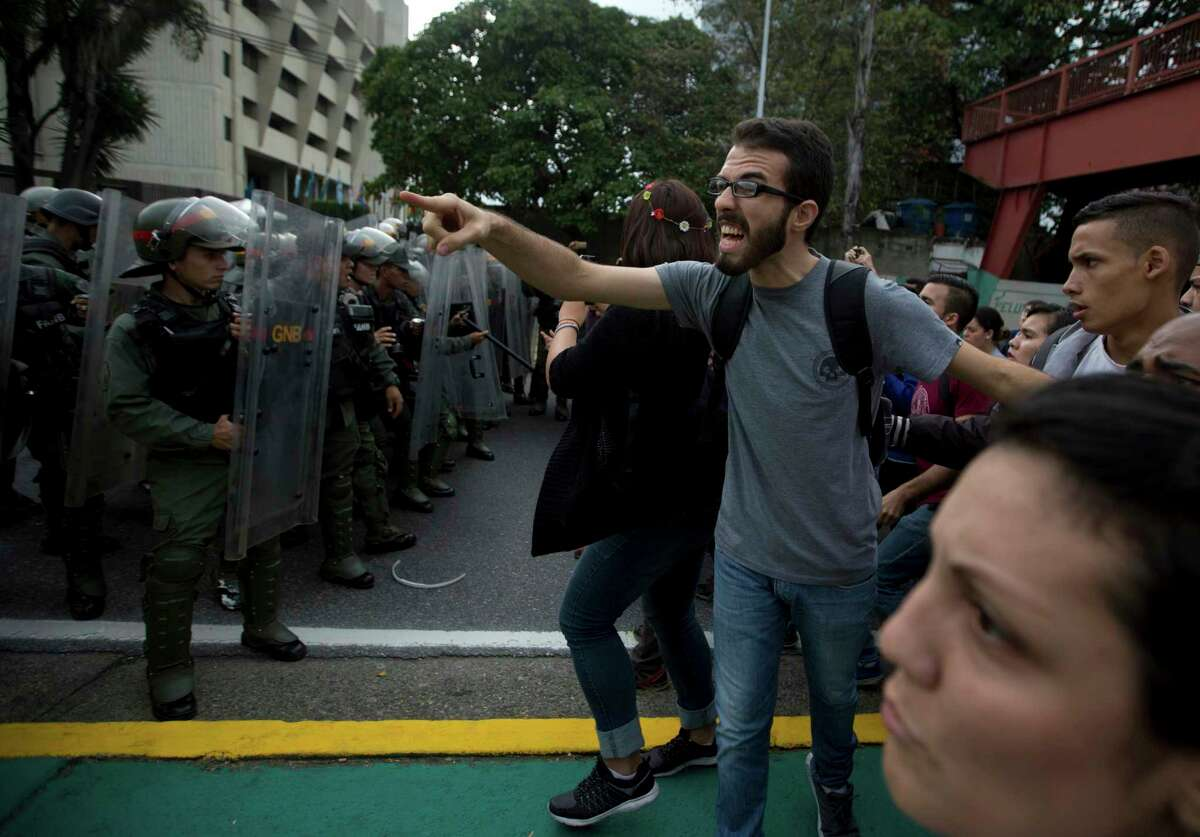 A university student shouts at a line of Venezuelan National Guard officers in riot gear during a protest Friday outside the Supreme Court in Caracas.