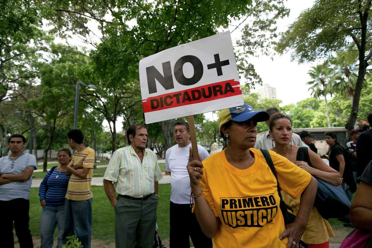 A woman holds up a sign that reads in Spanish read