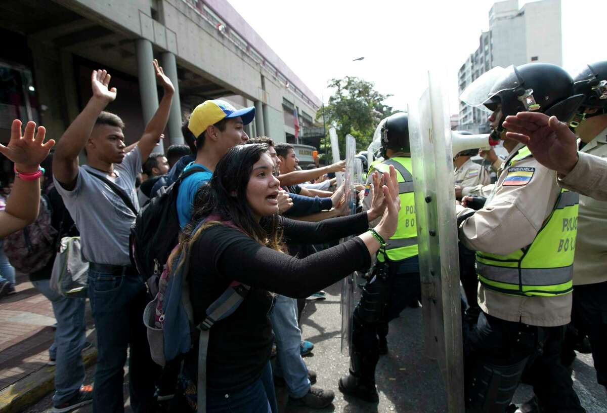 University students clash with Bolivarian National Police Officers during a protest outside of the Justice Palace in Caracas, Venezuela, Friday, March 31, 2017. Venezuelans have been thrust into a new round of political turbulence after the government-stacked Supreme Court gutted congress of its last vestiges of power, drawing widespread condemnation from foreign governments and sparking protests in the capital. (AP Photo/Ariana Cubillos)