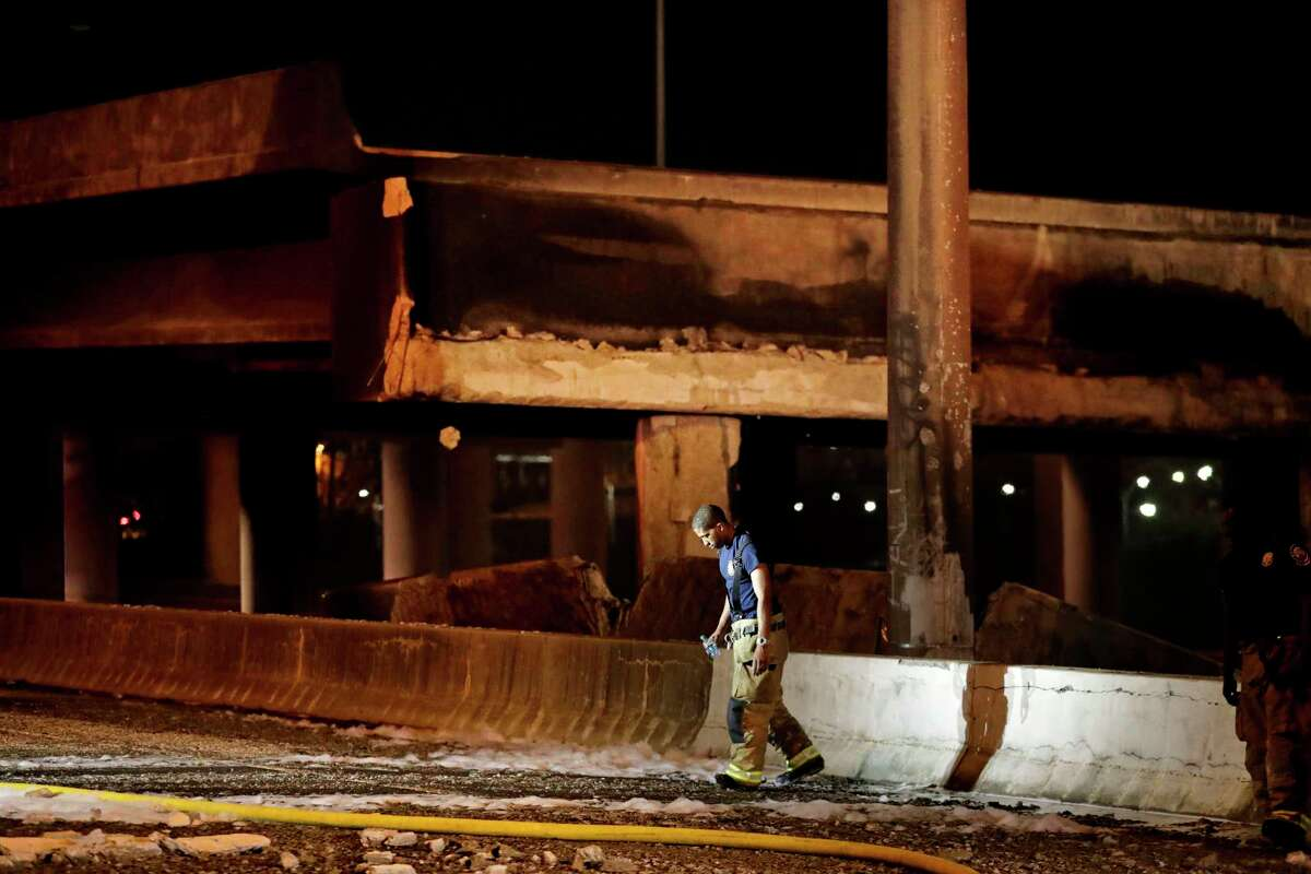 A firefighter walks by the section of an overpass that collapsed from a large fire on Interstate 85 in Atlanta, Thursday, March 30, 2017. Atlanta officials say a massive fire that burned for more than an hour caused the collapse of the interstate overpass. Georgia Gov. Nathan Deal has issued a state of emergency for the county. (AP Photo/David Goldman)