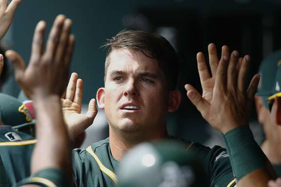 Oakland Athletics' Ryon Healy gets high-fives from teammates after scoring a run against the Chicago White Sox during the first inning of a spring training baseball game Wednesday, March 22, 2017, in Glendale, Ariz. (AP Photo/Ross D. Franklin)