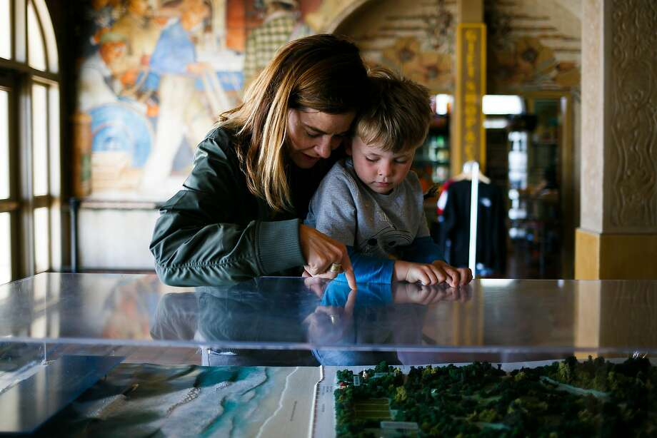 Kristen Sager holds up 5-year-old son Magnus Nyberg to look at the scale model of Golden Gate Park at the Beach Chalet. Photo: Mason Trinca, Special To The Chronicle