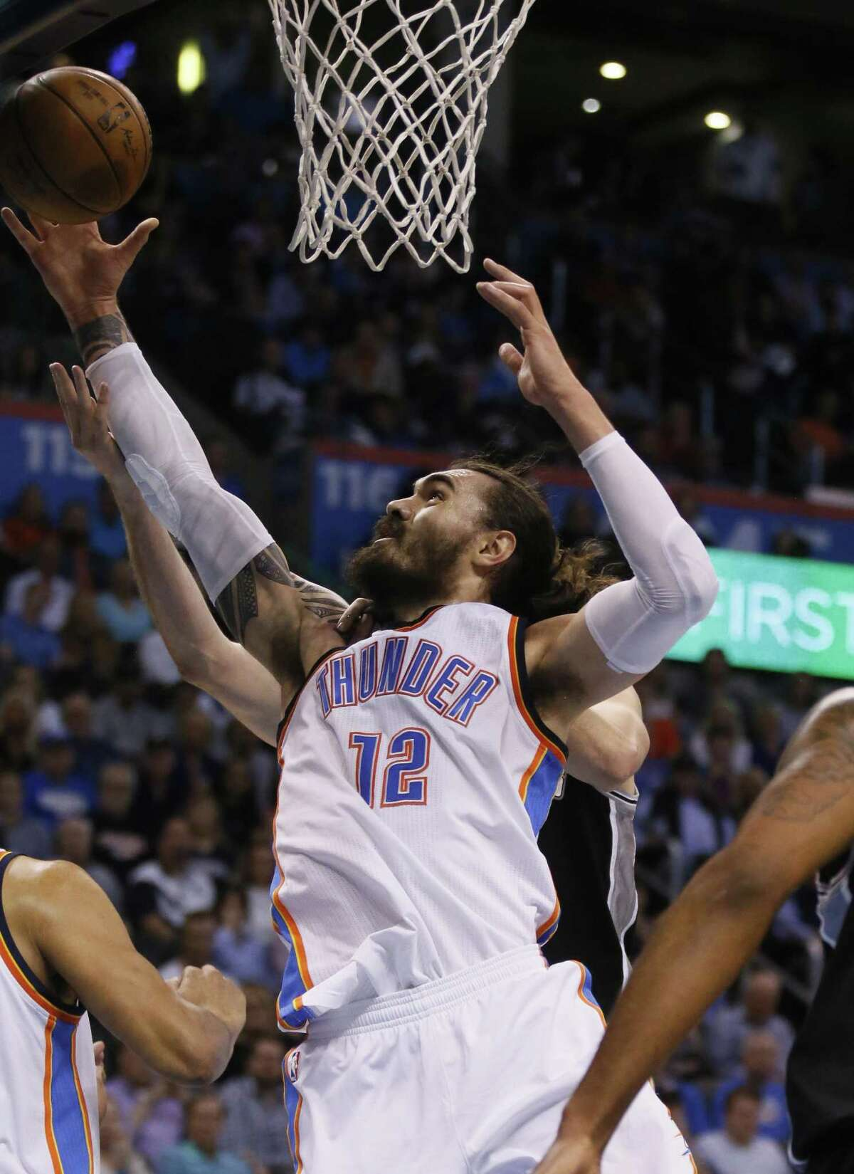 Oklahoma City Thunder center Steven Adams (12) grabs a rebound in front of San Antonio Spurs center Pau Gasol, rear, in the first quarter of an NBA basketball game in Oklahoma City, Friday, March 31, 2017. (AP Photo/Sue Ogrocki)