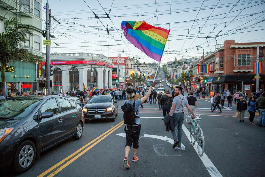 A woman who only gave her first name as Brandy waves a rainbow flag during a march and memorial in the Castro for Gilbert Baker on Friday, March 31, 2017, in San Francisco. Photo: Santiago Mejia, The Chronicle