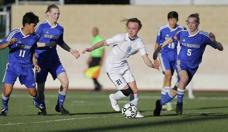 Johnson's Ashton Bynum (21) looks to manuever around New Braunfels defenders in 6A second-round boys soccer at Farris Stadium on March 31, 2017. Photo: Kin Man Hui /San Antonio Express-News / ©2017 San Antonio Express-News