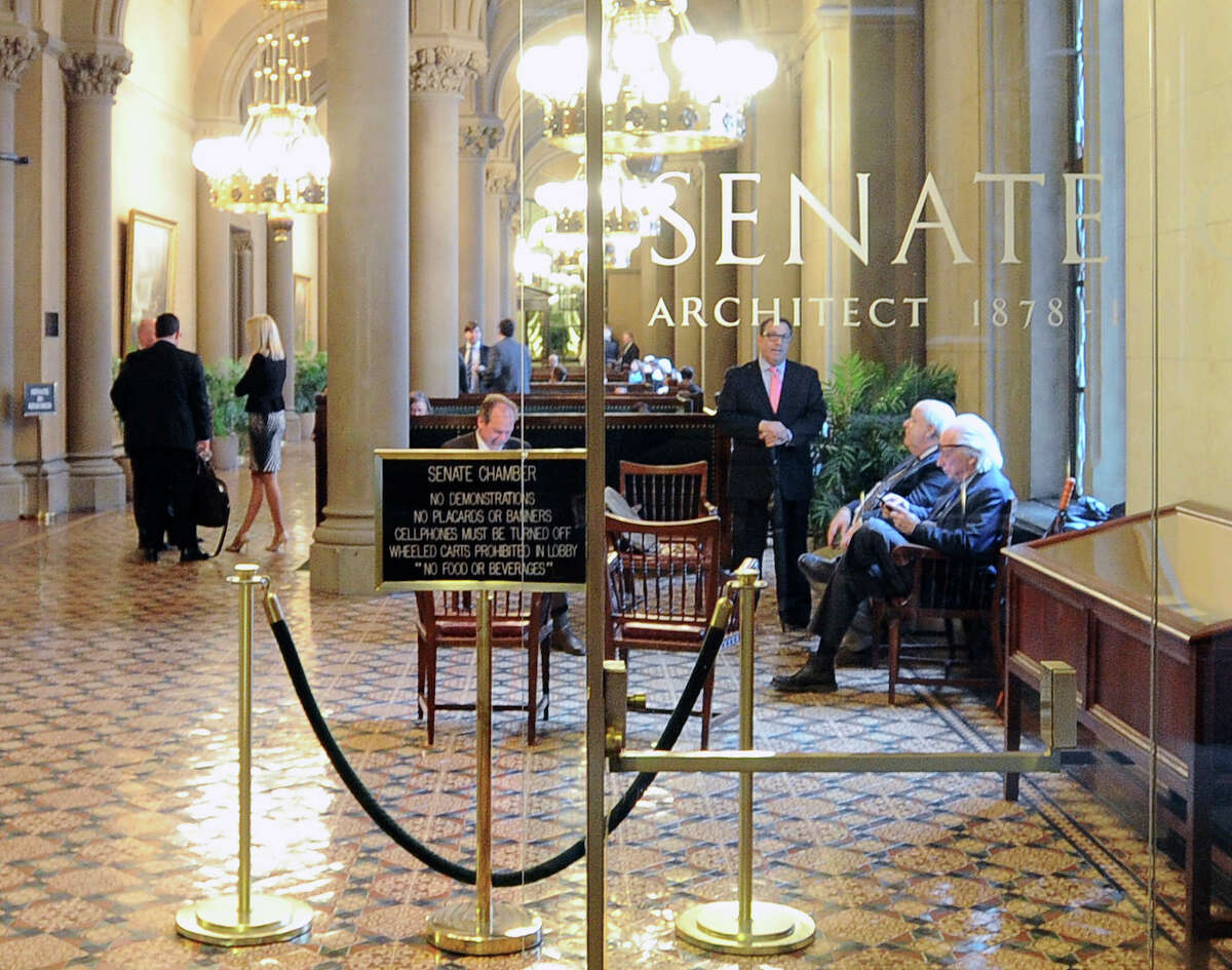 Lobbyists wait outside the Senate Chamber as legislative members work on the state budget at the state Capitol on Friday, March 31, 2017, in Albany, N.Y. (AP Photo/Hans Pennink) ORG XMIT: NYHP103