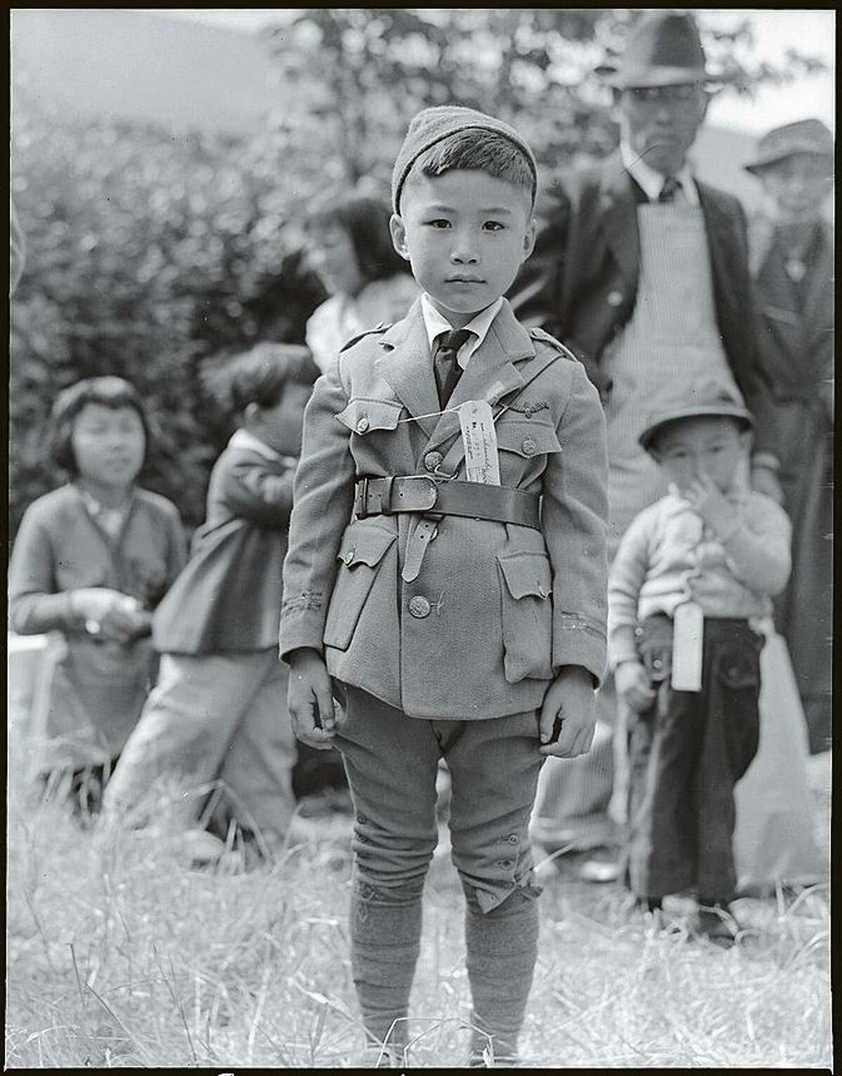 """Japanese American children wearing family identification tags as they wait to evacuate. Photo part of the ?""""Exclusion?"""" exhibition at the Presidio Officers?' Club from April 1, 2017 to March 2018."""