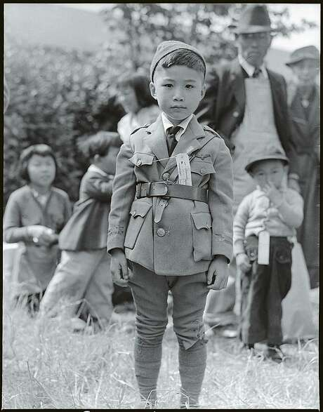 """Japanese American children wearing family identification tags as they wait to evacuate. Photo part of the """"Exclusion"""" exhibition at the Presidio Officers' Club from April 1, 2017 to March 2018. Photo: Photo Credit: Dorothea Lange, Centerville, California, May 9,1942 / Courtesy Of The National Archives And Records / ONLINE_YES"""