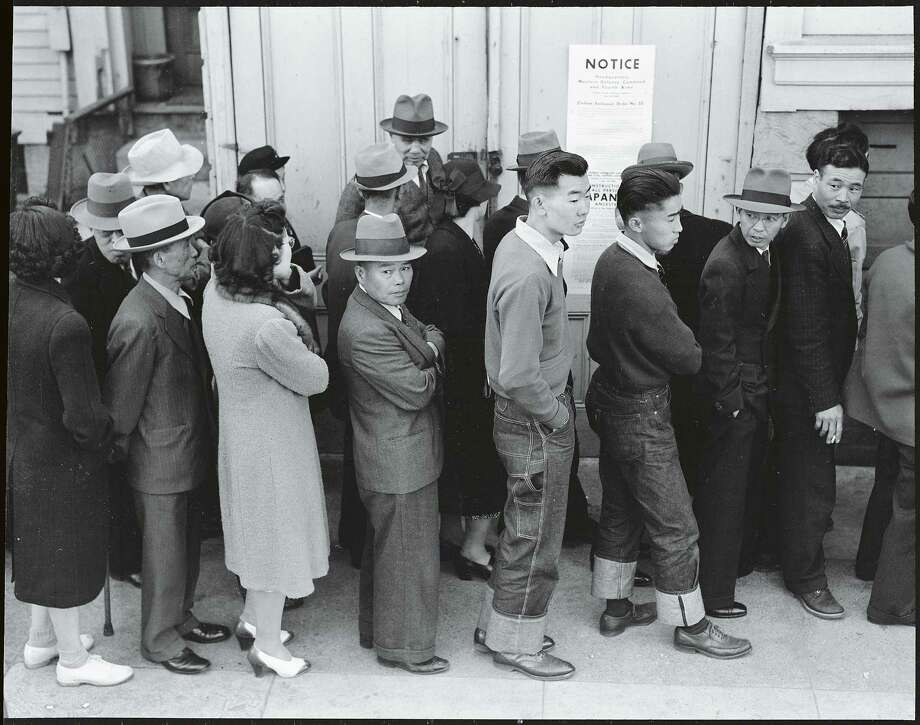 """Japanese Americans waiting in line to register for evacuation from San Francisco. Photo part of the """"Exclusion"""" exhibition at the Presidio Officers' Club from April 1, 2017 to March 2018. Photo: Photo Credit: Dorothea Lange, San Francisco, April 23, 1942 / Courtesy Of The National Archives And Records Administration / ONLINE_YES"""