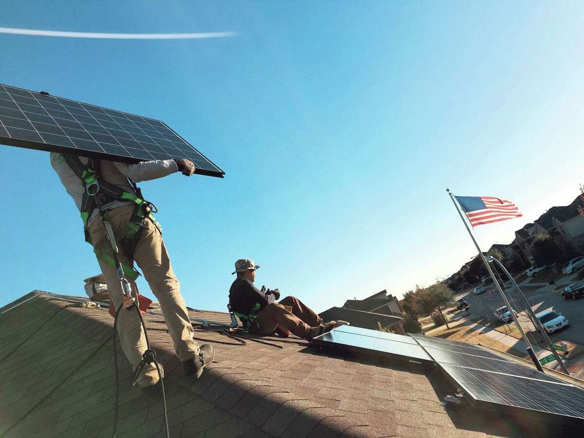 Workers install a SolarCity rooftop solar system at a home in the Dallas area. SolarCity is about to enter the Houston market.