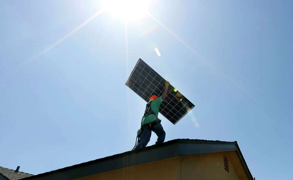 **EMBARGO: No electronic distribution, Web posting or street sales before 12:01 a.m. ET Wednesday, Oct. 8, 2014. No exceptions for any reasons. EMBARGO set by source.** A SolarCity employee works on a solar panel installation at a home in Camarillo, Calif., June 27, 2014. SolarCity, which became the nation's largest rooftop solar installer by leasing the equipment to their residential customers, is going to start allowing them to buy the systems outright, with payments based on how much electricity their system is producing. (J. Emilio Flores/The New York Times)