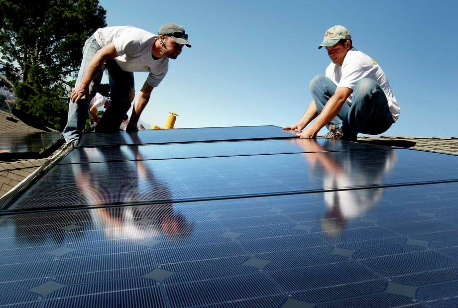 Solar installers Frank Teague, (left) and Delmar Oliveira positioned panels on the Oakland rooftop.  Photo: Brant Ward, Staff Photographer / MANDATORY CREDIT FOR PHOTOG AND SAN FRANCISCO CHRONICLE/NO SALES-MAGS OUT-INTERNET OUT-TV OUT-ONLINE YES